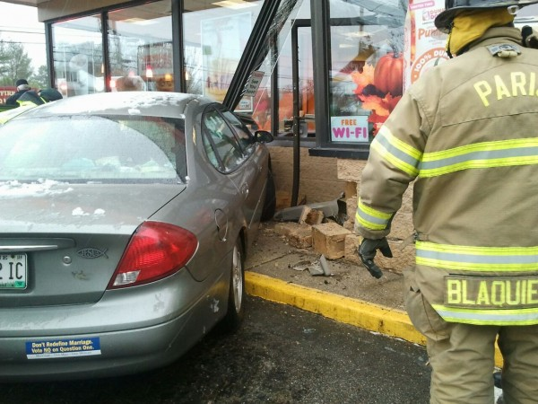 A firefighter examines the scene where a car collided with the entrance of a Dunkin' Donuts in Paris.