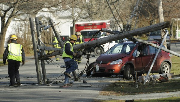 Electrical workers inspect a pole that was knocked over by a driver along 13th Street in Bangor on Tuesday, Nov. 27, 2012. The driver was handcuffed and taken from the scene by Bangor police.