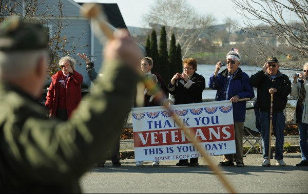 The Maine Troop Greeters wave to veterans as they cross the Joshua Chamberlain Bridge in Brewer on Monday, Nov. 12, 2012, during the Bangor-Brewer Veterans Day parade.