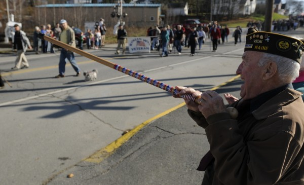 Robert Glidden uses his walking stick to salute fellow WWII veterans as they march in the Bangor-Brewer Veterans Day parade in Brewer on Monday, Nov. 12, 2012.