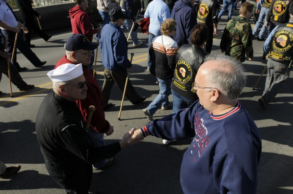 Joe Leveille (right) of Orono greets and thanks veterans for their service as they cross the Joshua Chamberlain Bridge in Brewer on Monday, Nov. 12, 2012, during the Bangor-Brewer veterans Day parade.