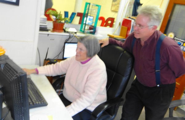 Anne Allee, a volunteer for Belfast Community Media, works at archiving community TV video clips as Ned Lightner, Belfast Community TV director, looks on.