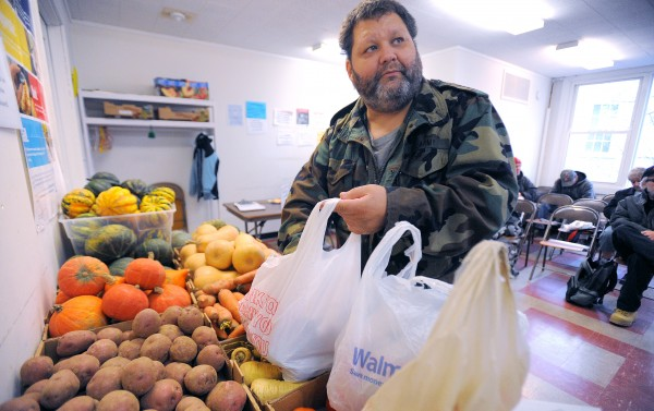 Gus Edgerton of Bangor packs vegetables while picking up food at the Hammond Street Church Ecumenical Food Cupboard on Wednesday.  Edgerton