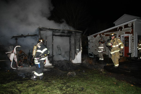 Rockland Fire Department Lt. Rick Johnson (from left), Assistant Chief Adam Miceli and firefighter Mike Cole douse a fire that destroyed a shed on Berkley Street in Rockland on Tuesday night.