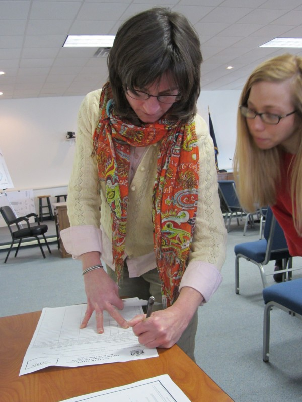 Elizabeth Dickerson fills out paperwork at the Democratic caucus in Rockland in February 2012.