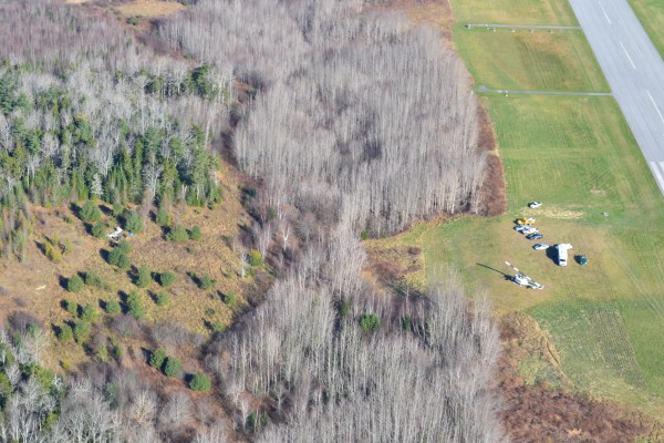 The wreckage of a plane that crashed Friday evening at the Knox County Regional Airport is seen to the left of the airfield and recovery crews.