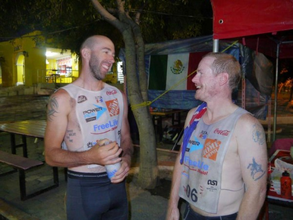After spending more than 12 days swimming, cycling and running, Turner athlete Kale Poland (left) spends a moment at the finish line with fellow racer Simon Bourne of Great Britain after the two men completed the grueling decatriathlon.