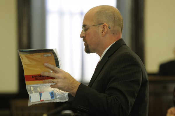 Assistant Attorney General Donald Macomber holds the bullet that was removed from Everett Cameron's brain during opening arguments in the murder trial of Robert Lee Nelson of Norridgewock in Somerset County Superior Court in Skowhegan on Monday, Nov. 26, 2012. Nelson is accused of shooting Cameron for drugs.