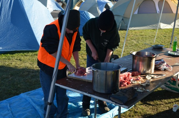 Two members of Boy Scout Troop 63 cut meat to prepare for a beef stew meal as part of a camping outing to collect food for the Newport Community Food Bank on Saturday, Nov. 10, 2012.