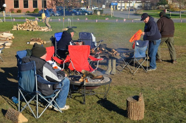 Members of Boy Scout Troop 63 gather around camp fires to warm up during a camping outing in front of Bud's Shop & Save in Newport on Saturday, Nov. 10, 2012. The troop is collecting food donations for the Newport Community Food Bank.