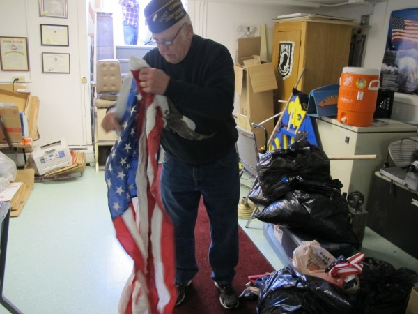 Louis Tonero, quartermaster for VFW Post 109 in Ellsworth, displays a worn flag at the VFW Hall in Ellsworth on Sunday.