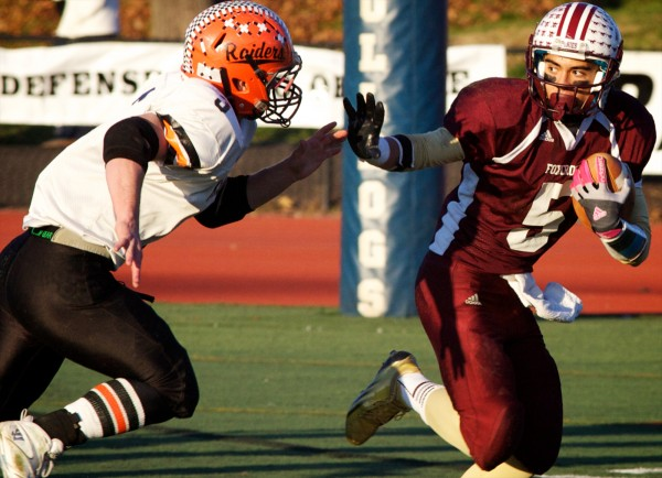 Foxcroft Academy wide receiver Ryan Rebar (5) wards off a defensive player from Winslow in the Class C football state championship game Nov. 16 in Portland. The Maine Principals' Association Football Committee has recommended a realignment of teams into four classes for 2013.