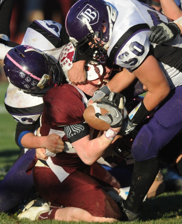 John Bapst players Brad DeCesere (left) and Charles Kindya rip and tug at Foxcroft Academy Pony Peter Boyer as they tackle him during 4th quarter action at Dover-Foxcroft on Saturday, Nov. 10, 2012. Foxcroft won 33-7.