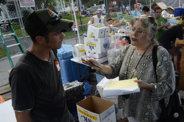 Michele Sturgeon, Portland's food service industry health inspector, talks to Anthony Salvaggio, owner of The Maine Squeeze lemonade stand, on the Eastern Promenade in August during the Gentleman of the Road festival.