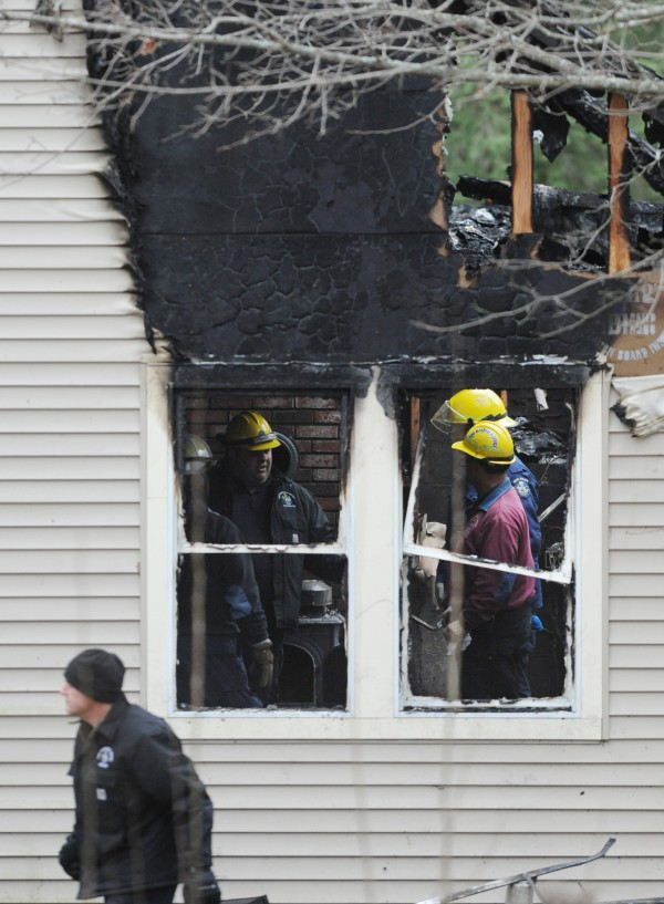 A team of state police and fire marshals confer in the living room of the house at 580 Dow Road in Orrington on Sunday, Nov. 11, 2012.