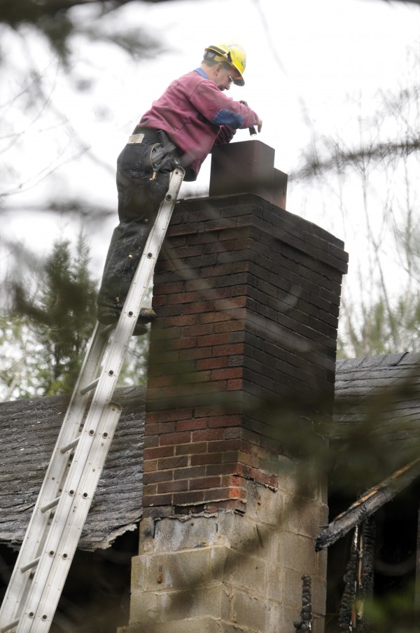 Fire Marshal Ed Archer looks down the chimney of the house at 580 Dow Road in Orrington on Sunday, November 11, 2012 as a team of state police and fire marshals try to determine the cause and origin of the fire that took the life of one man and three children early Saturday morning.