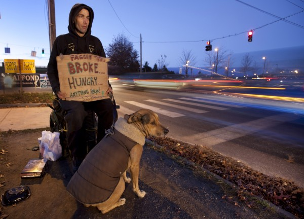 "Liam O'Reilly, 30, sits with his dog, Tiberius, while asking for help on Marginal Way in Portland on Monday evening. O'Reilly and his dog hop freight trains to travel around the country. His previous dog was killed by the police in New Orleans. &quotThey'€™re a really violent police force. I was spare-changing. They came up and started giving me [a hard time], started beating me up. My dog didn'€™t really stand for that so she bit one of them. They shot her five times. I punched about about three cops, which is not very smart —€"" punching cops with guns —€"" but the judge threw it out because they used excessive force,&quot he said."