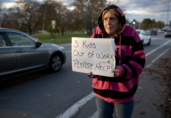 Kim Lang, 46, holds a sign on State Street in Portland. &quotThis is my first time. I have someone watching my kids [ages 6, 8 and 12] right now. My apartment caught on fire. Had carbon monoxide poisoning. Thank God my kids weren'€™t there. I've been trying to get my own place but it's hard with certain limitations on income,&quot she said.  &quot[The motorists] are being very generous, I'€™m surprised, actually. It's greatly appreciated.&quot