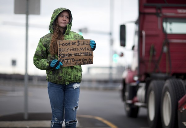 Shay, 26, holds a sign asking for money to help feed her four kids on West Commercial Street in Portland. She has two sets of twins, 1-year-old boys and 5-year-old girls. &quotI pay my rent with the money that I make from my part-time job [at a Wendy's]. I come out here to make the rest for food. I hate being out here,&quot she said. &quotMy daughter got sick [with bacterial meningitis], I lost one of my part-time jobs, and LePage cut me off. Boom, boom, boom. I don'€™t get food stamps, but I get MaineCare for my children. I did not collect unemployment because I'm stronger than that. €œI a€™m part of the 66 percent of women who have been cut off by LePage. For him, I say, 'You suck.' I work hard, and I have always worked hard. I'€™m only 26 years old. And that's not cool.&quot€