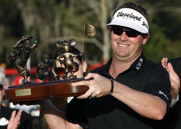 Charlie Beljan holds up the trophy on the 18th green after winning the Children's Miracle Network Hospitals golf tournament in Lake Buena Vista, Fla., Sunday, Nov. 11, 2012.