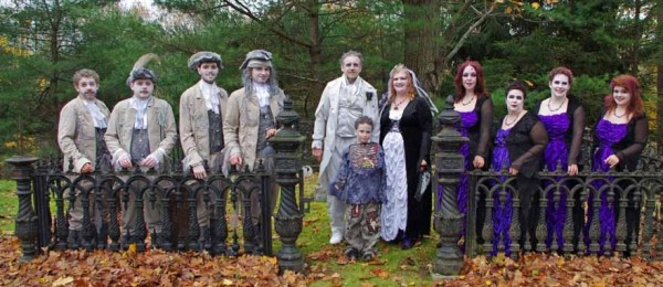 "Members of the Charlie and Pam King wedding party, dressed in their zombie pirate and ""goddess of darkness"" attire, pose at the entrance of a cemetery for a wedding photo — (from left) Justice King, son of the groom; Paul Sabatino, groomsman; Chrys Towne, son of the bride; Jason Tenney, best man; Charlie King, groom; Izzy Tenney, son of Jessica and Jason Tenney; Pam King, bride; Jessica Tenney, maid of honor; Rhonda Cyr, bridesmaid; Susan Wheaton, bridesmaid; and Toni Marie Towne, daughter of the bride."