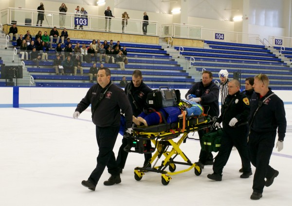 First responders leave the hockey arena ice at the University of New England in Biddeford on Friday, Nov. 16, 2012 with a life-like simulation dummy with a spinal injury during a demonstration.