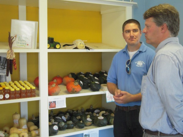 John Piotti, executive director of the Belfast-based Maine Farmland Trust (right), listens intently as Farm Manager John Hoffses describes the products offered in the MSAD 1 Farm Store in Presque Isle.