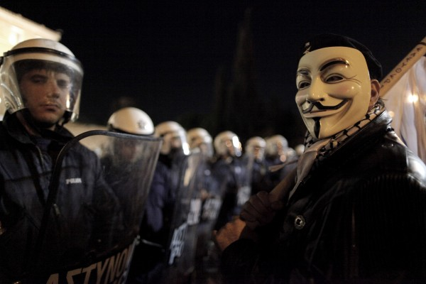 A demonstrator wearing an anti-establishment Guy Fawkes mask, stands next to riot police that secure the Greek parliament during an anti- austerity rally in central Athens on Sunday Nov. 11, 2012.  Greece's lawmakers were set today to pass next year's austerity budget, extending tough spending cuts measures that have already left Greeks struggling as the country tries to slash its debts and pull itself out of a severe recession.