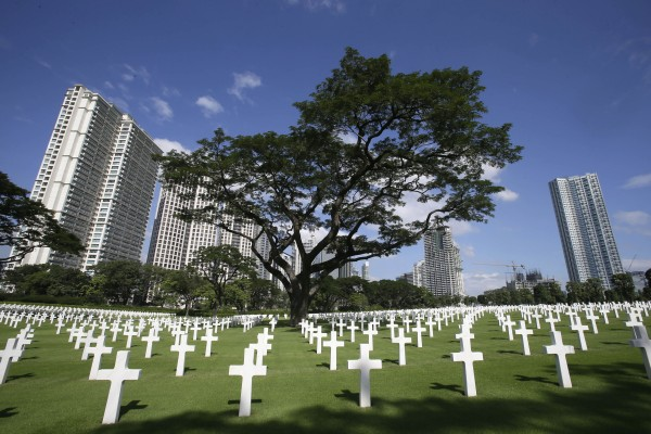 Rows of crosses totaling 16,933 Latin crosses, 164 Stars of David and 3,740 unknowns, dot the 152-acre American Cemetery as U.S. and Filipino WWII veterans and other officials (unseen) commemorate U.S. Veterans Day at the American Cemetery at suburban Taguig city, east of Manila, Philippines Sunday, Nov. 11, 2012.