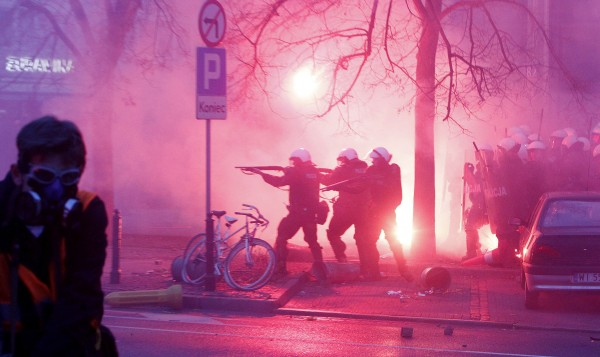 Police try to secure the area during clashes at  the March of Independence  to mark Poland's Independence Day, in Warsaw, Poland, Sunday, Nov. 11, 2012. A  Police spokesman says that two officers have been injured in a brief clash with hooligans in which police fired rubber bullets and used tear gas during a right-wing march to mark Poland's independence day. Earlier, thousands of people walked peacefully in another march, led by President Bronislaw Komorowski, and in smaller marches backed by various political options. Last year, many police officers were injured and there was damage in the streets when right-wing marchers clashed with opponents and police.