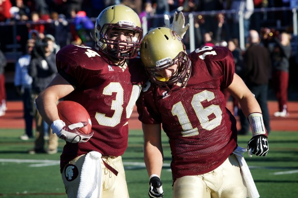 Thornton Academy full back Nick Kenney (34) congratulates Andrew Libby (16) after he scored a touchdown in the Class A Football State Championship game in Portland.