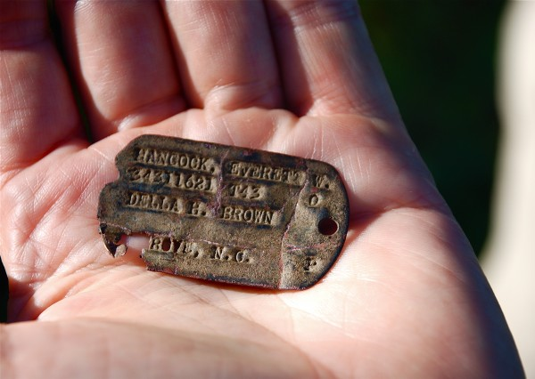 Anderson Giles, a professor at the University of Maine at Presque Isle, holds a dog tag belonging to Everett W. Hancock of North Carolina, who served in combat. It was found on Guadalcanal.
