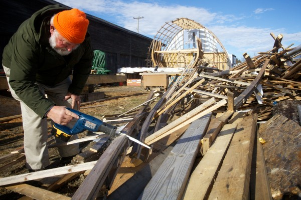 Orman Hines of Maine's First Ship cuts up rubble on Friday in Bath from a temporary boat shed that blew down in Hurricane Sandy. The shed covered the yet unfinished reproduction of the Virginia, the first European designed ship built in Maine by the Popham Colonists in 1608.