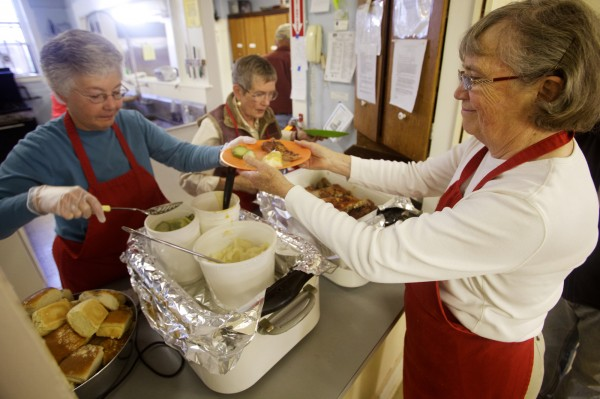 Bonnie McDonald (left) puts mashed potatoes on a plate for fellow volunteer Jean Tompkins (right) at the Bath Area Food Bank's thrice weekly free lunch in the basement of the First Baptist Church in Bath on Friday Nov. 9, 2012. The soup kitchen reopened three weeks ago after being shuttered for six weeks.