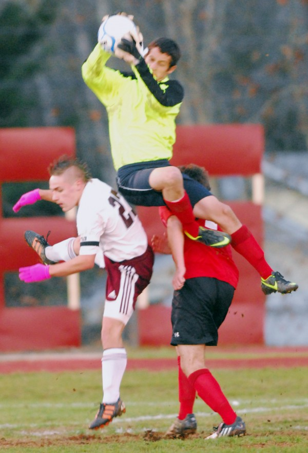 Camden Hills goalie Marshall Spear leaps to control the ball over Ellsworth's Maks Grover (left) and a Camden Hills player in first-half action of their Eastern Maine Class B final in Ellsworth on Thursday, Nov. 1, 2012.