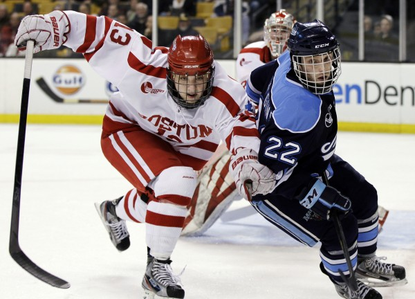 Boston University's Garrett Noonan (13) defends against Maine's Stu Higgins (22) during a game in the Hockey East tournament last March in Boston. Higgins suffered a leg injury in Sunday's game against New Hampshire and might not play in Maine's weekend series against Lowell.