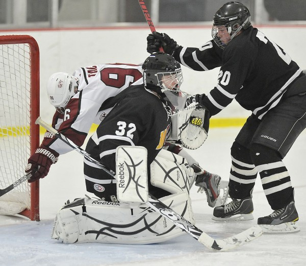 Maranacook goalie Tyler Plante (32) focuses on the action as teammate Ian Palmer (20) works on Bangor forward Jordan Tracy (96) in a game in Bangor last season.