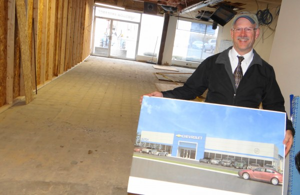 Greg Dutch, the principal owner of Dutch Chevrolet, holds up an artist's rendering of what the Belfast dealership will look like after a make-over is completed.
