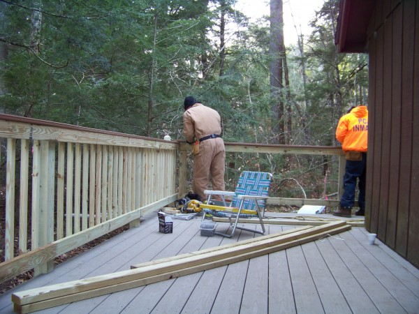 As part of a Community Works Project, inmates from  Penobscot County Jail in Bangor work Thursday, Nov. 29, on building a deck around the bunkhouse at Camp CaPella in Dedham.