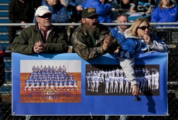 Tim Robinson (left), Paul Carl and Doris Champagne, cheer behind a banner showing the team photo and the team at prayer before game, during the state championship game Saturday, Nov. 17, 2012, at Fitzpatrick Stadium in Portland.