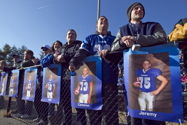 Portraits of the team's 19 seniors hang on a fence in front of the bleachers at the state championship game Saturday, Nov. 17, 2012, at Fitzpatrick Stadium in Portland.