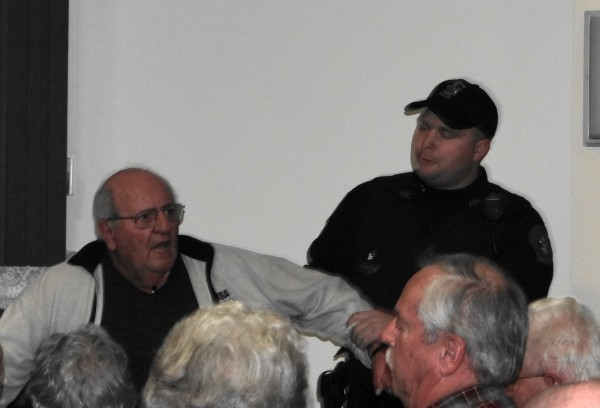 A Searsport police officer attempts to escort resident Ben Crimaudo from the Searsport Planning Board's Wednesday night meeting at which it reviewed the proposed 23-million gallon propane tank.