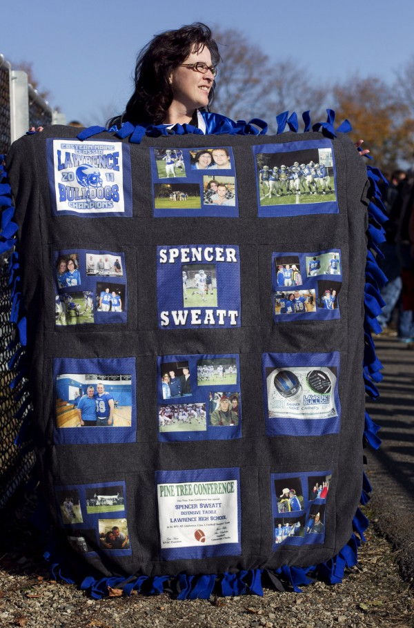 April Sweatt displays a blanket commemorating her son Spencer's football career as a Lawrence Bulldog, at the state championship game Saturday, Nov. 17, 2012, at Fitzpatrick Stadium in Portland.