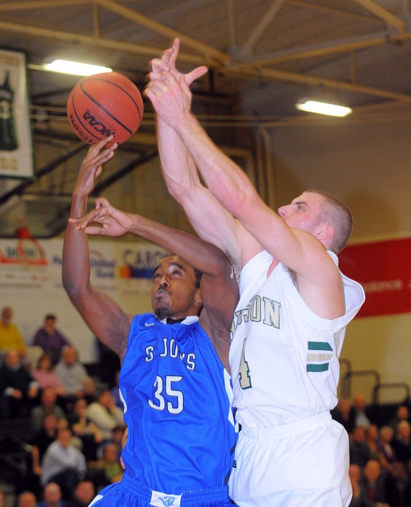 Husson University's Brooks Spaulding (right) and Saint Joseph's College's Krubiel Workie scramble for a rebound during the first half of the game at Husson University in Bangor on Thursday evening, Nov. 29, 2012.