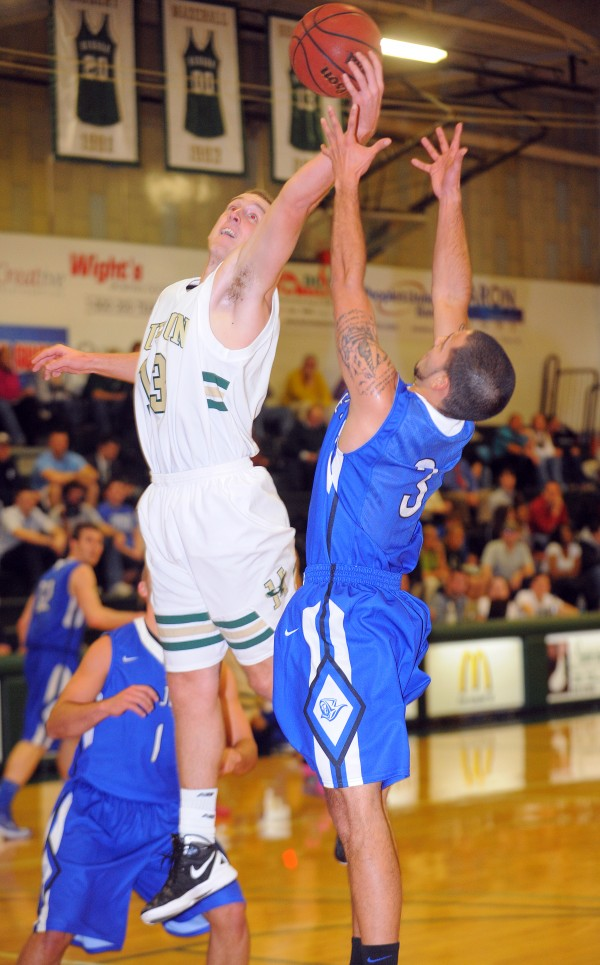 Husson University's Jacob Moore (left) goes up for a rebound over Saint Joseph's College's Julio Vazquez during the first half of the game at Husson University in Bangor on Thursday evening, Nov. 29, 2012.