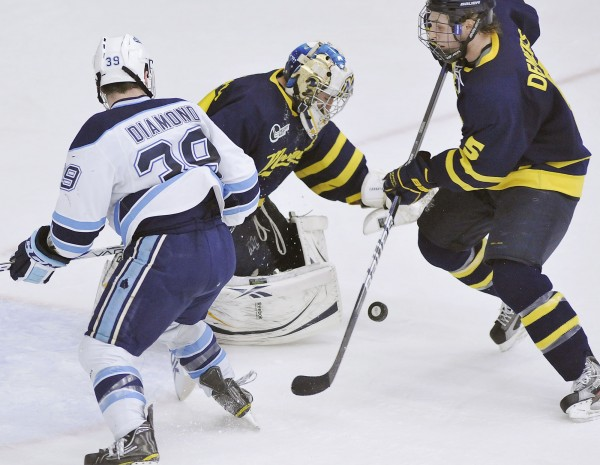 Merrimack goalie Joe Cannata and defenseman Simon Demers (5) play a puck shot by Maine winger Joey Diamond (39) during a game last March. Diamond, who had 25 goals and 22 goals last season, is in a scoring slump and has only one goal and three assists in 11 games this season.