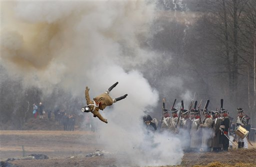 Men dressed as 1812-era Russian and French soldiers re-enact a staged battle as a dummy soldier is blown up,  near the Belarus village of Bryli, about 70 miles east of the capital, Minsk on Saturday, Nov. 24, 2012, to mark the 200th anniversary of the Berezina battle during Napoleon's army retreat from Russia. The retreat across the Berezina of the remnants of Napoleon's Grand Army, which invaded Russia June 24, 1812, took place from Nov. 26 to Nov. 29, 1812. About 50,000 people, soldiers from both sides and civilians, were killed during the crossing, which was effected under heavy Russian attack and saved Napoleon and his forces from capture. In total of nearly half a million soldiers, from France as well as all of the vassal states of Europe, who invaded Russia in June, barely 10,000 survived by the end of the campaign, December 1812.