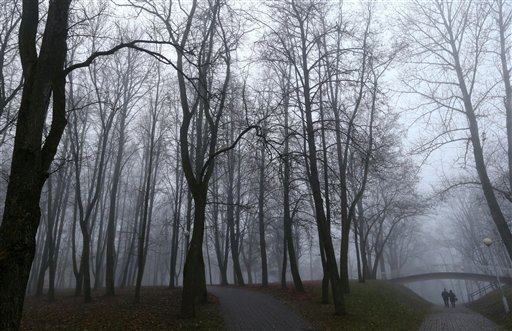 People walk in a park on a foggy day as the temperature hovers at around 39 Fahrenheit in Minsk, Belarus on Tuesday, Nov. 27, 2012.