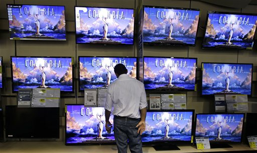 A shopper looks at televisions at a Best Buy store, Friday, Nov. 23, 2012, in Franklin, Tenn., after the store opened at midnight. Black Friday, the day when retailers traditionally turn a profit for the year, got a jump start this year as many stores opened just as families were finishing up Thanksgiving dinner.