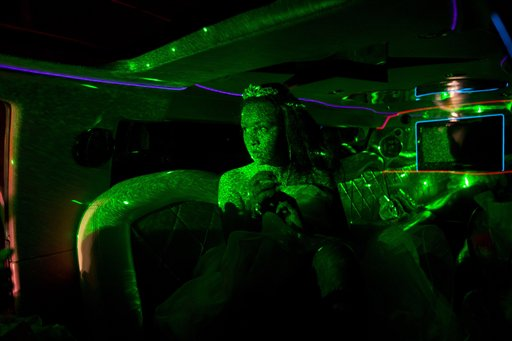 A girl turning 15 is bathed in green light inside a limousine as she arrives for a group debutante ball, organized by the Peacemaker Police Unit program in the Mangueira favela, or shantytown, in Rio de Janeiro, Brazil on Thursday, Nov. 8, 2012. The debutante ball marks girls' transition from childhood to adulthood and is common in Brazil and other Latin American countries.